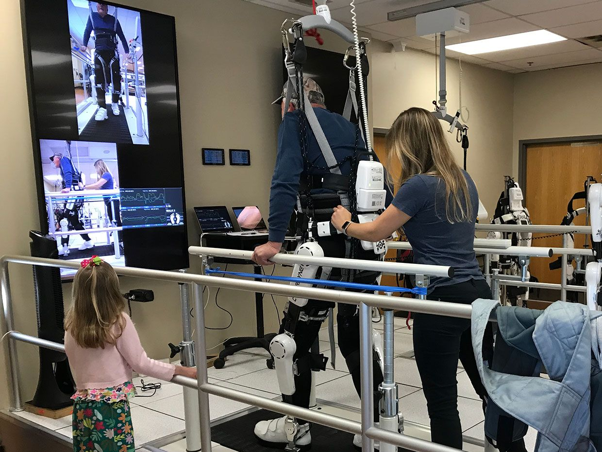 Danny Bal completes a treatment session with the Cyberdyne HAL exoskeleton at Brooks Rehabilitation in Jacksonville, Florida as his granddaughter cheers him on.