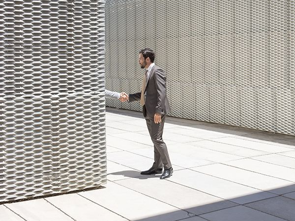 A photo shows a man in a grey suit shaking hands with someone who is hidden around the corner in an outdoor scene.
