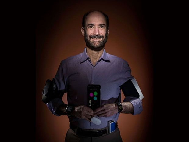 Stanford research Michael Snyder poses laden with the wearable gadgets that recently helped him realize he'd been infected by Lyme disease before he showed symptoms