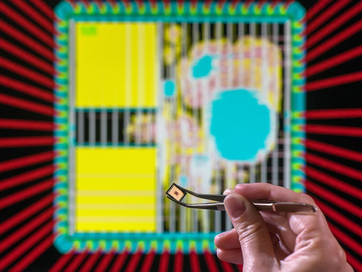 A chip is held with tweezers by a hand.