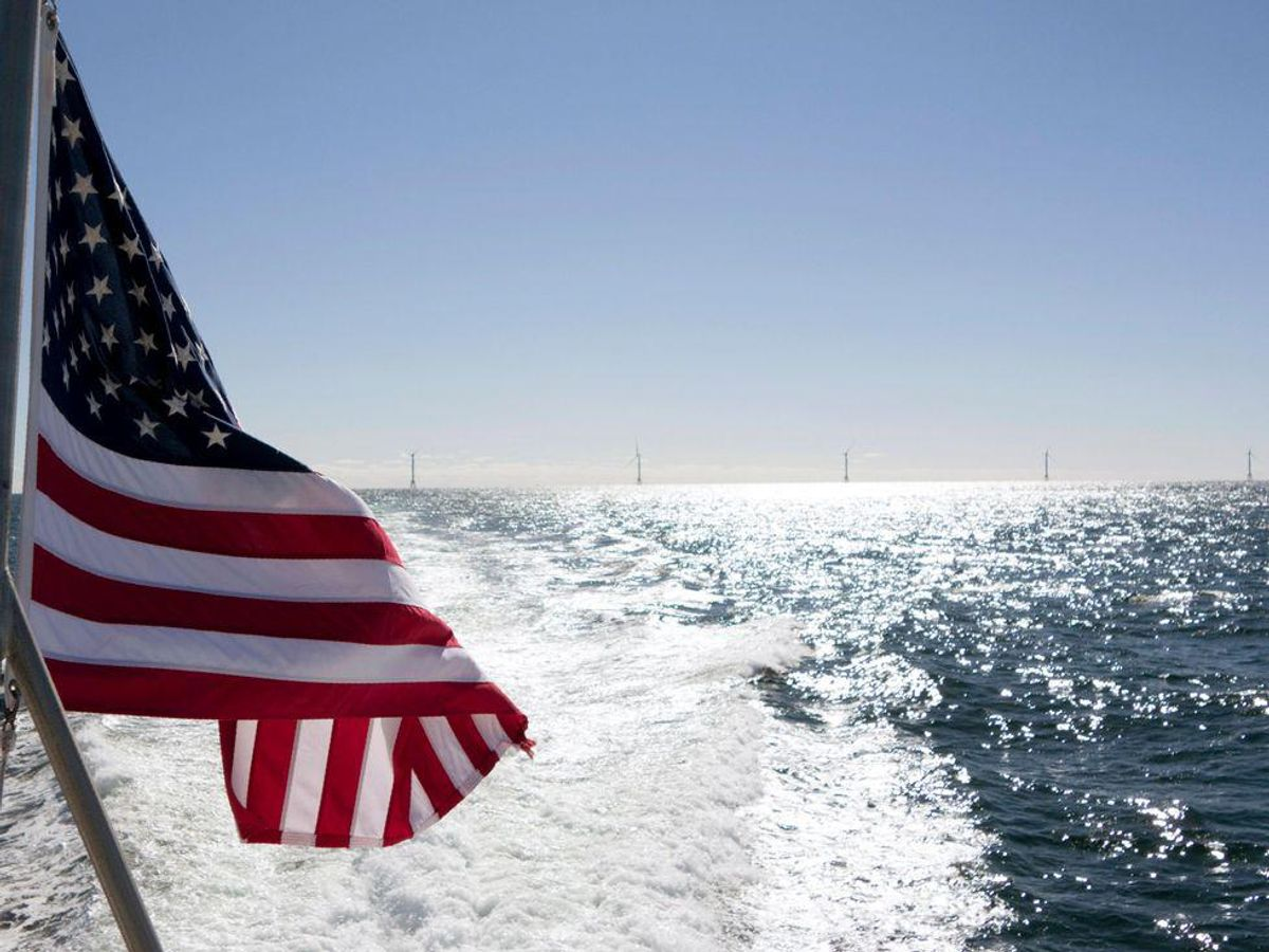 An American Flag in the foreground with water and wind turbines in the distance.