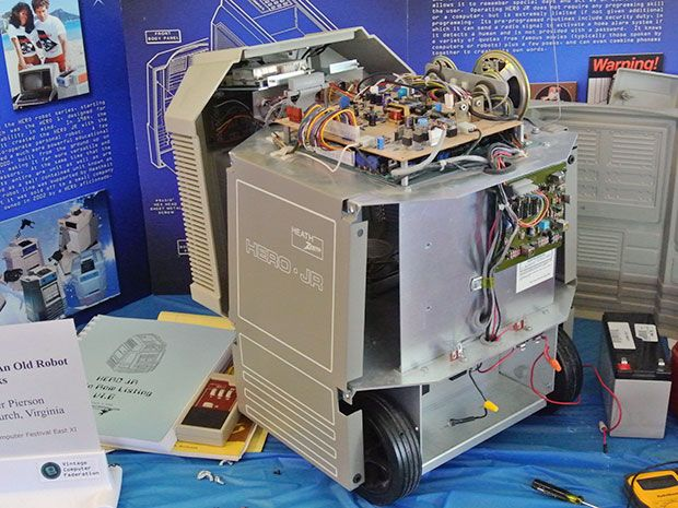 A squat gray robot with its covers removed. Two wheels and some circuit boards are visible.
