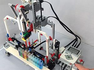A lego structure with wires and colored liquids in a test tube