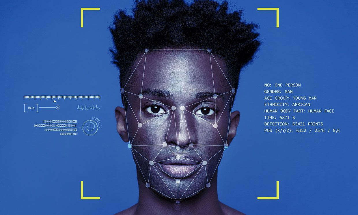 Photo-illustration of a man of color with facial recognition technology reading his face.