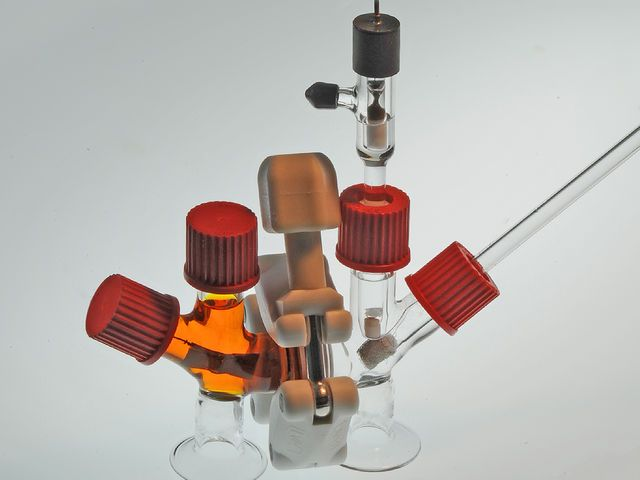 "A photo shows an ""air-breathing"" battery made of clear glass tubins with red caps and an orange liquid in one half."