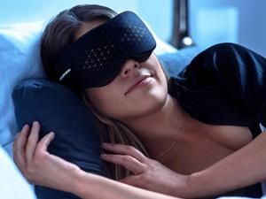 A woman sleeping in bed wearing a black eye mask