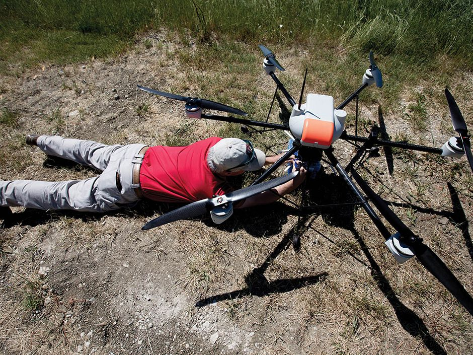 Maurice Griffin, a drone pilot, screws a GreenCell base station to the bottom of an AR200 drone.