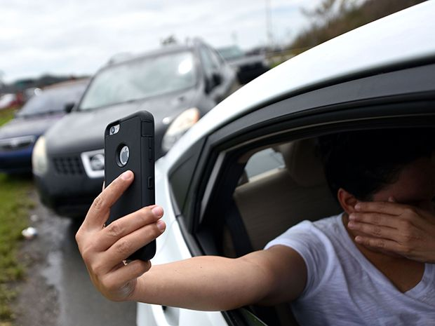 A photo of a woman sitting in her car trying to make a call on a smartphone in Puerto Rico following Hurricane Maria.