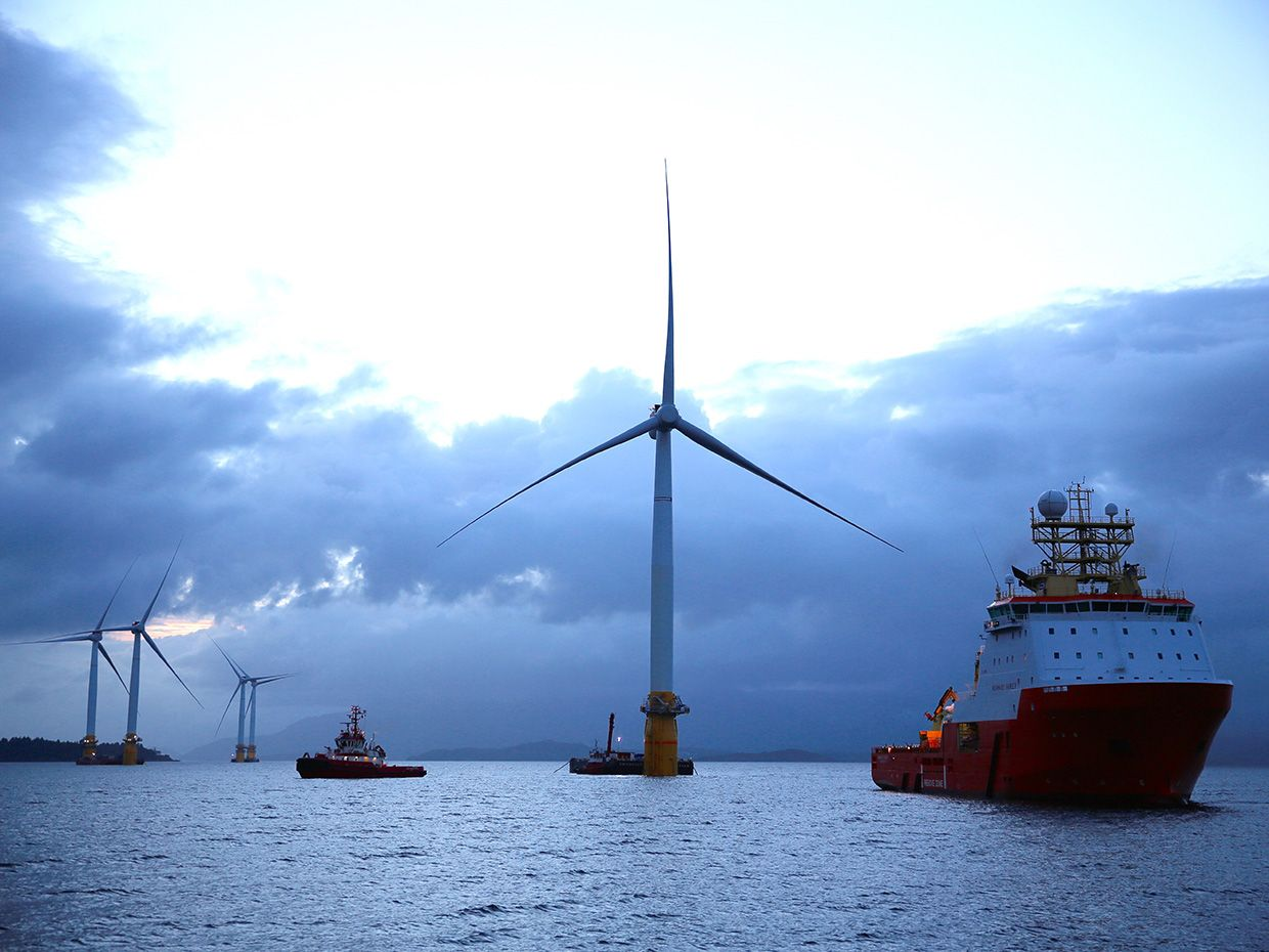 A photo shows several of Statoil's floating wind turbines surrounded by ships at dusk.
