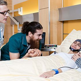 A woman lies in a hospital bed with the mindBEAGLE EEG headpiece on, surrounded by two family members and a doctor.