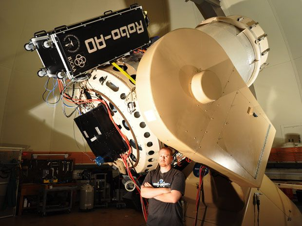 Giant telescope with scientist standing in front of it