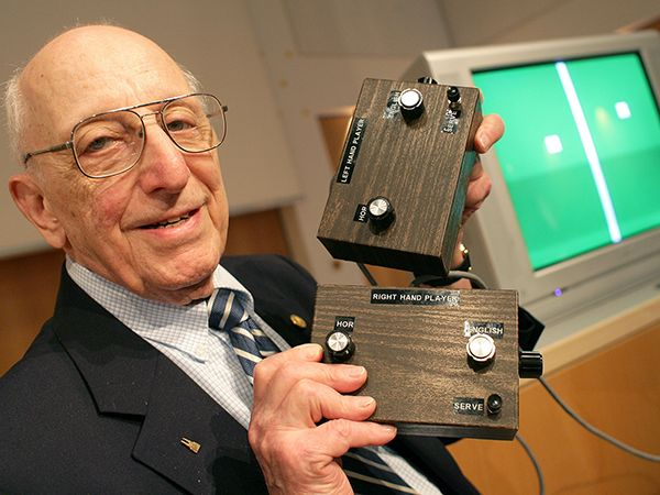 2009 photograph of game developer Ralph Baer holding his Brown Box game, with a TV with pong on the screen in the background.
