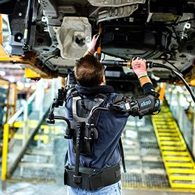 A worker on a car assembly line works on the chassis above his head. He's wearing an upper-body exoskeleton that has components around his arms and down his back.
