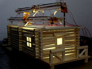 A model house with wind and solar energy devices.