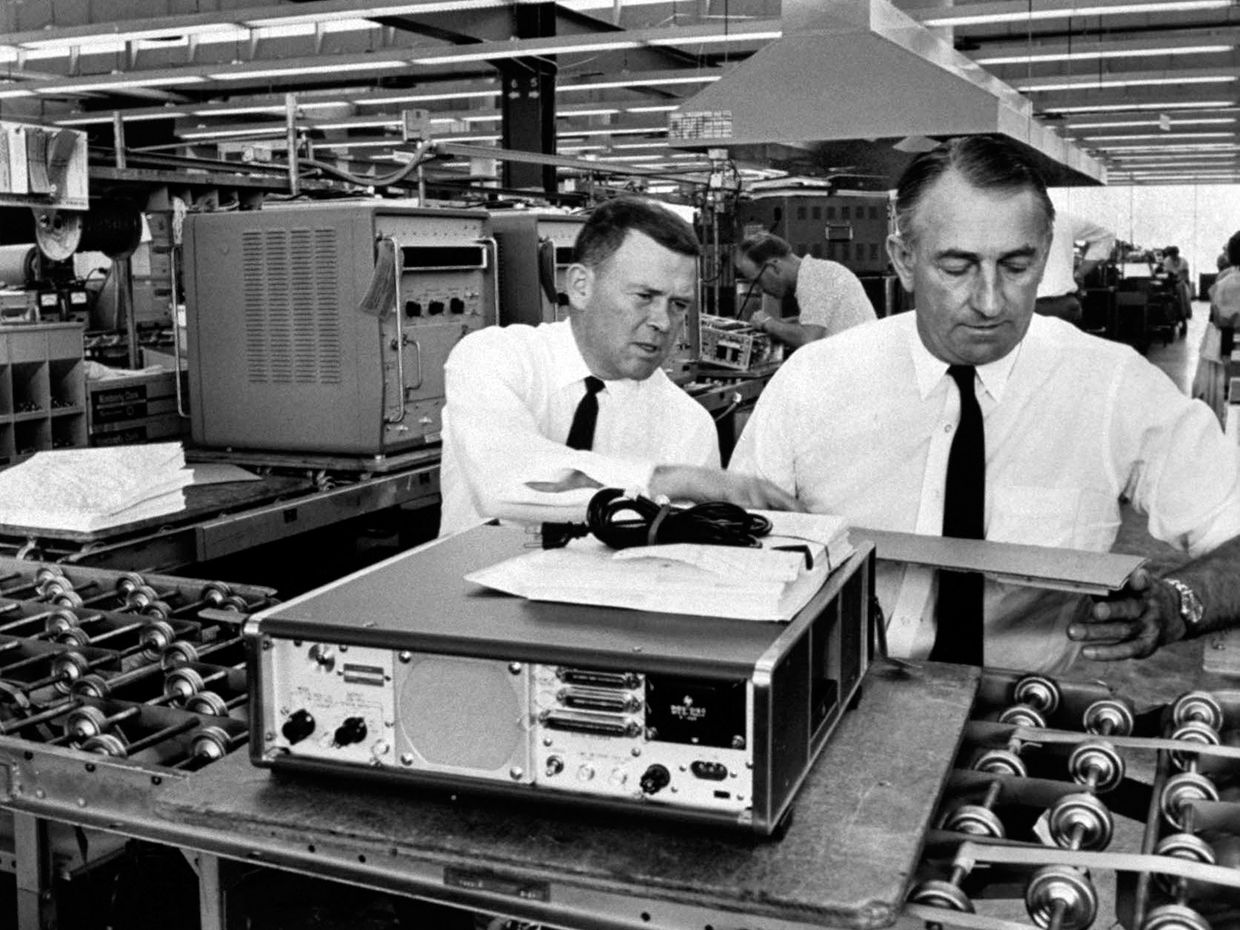 A black-and-white photo shows Hewlett Packard founders William Hewlett and David Packard in a factory.