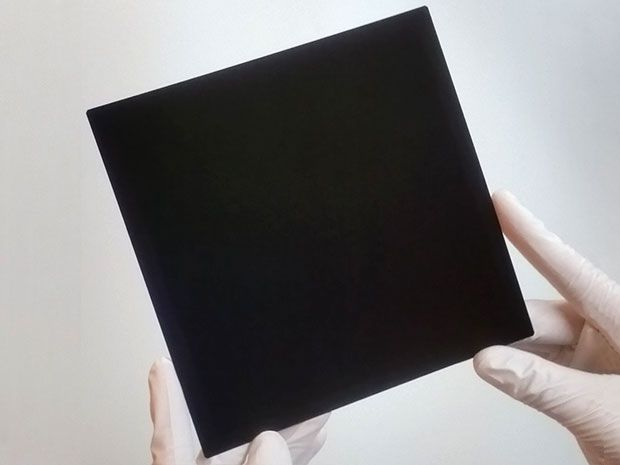 Latex gloved hands holding a foot-wide black square