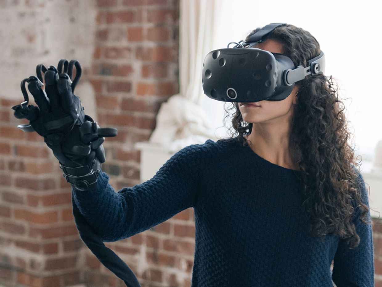 A photo shows a woman wearing the new HaptX glove, which resembles a large black ski glove with wires attached to it, and an HTC Vive headset.
