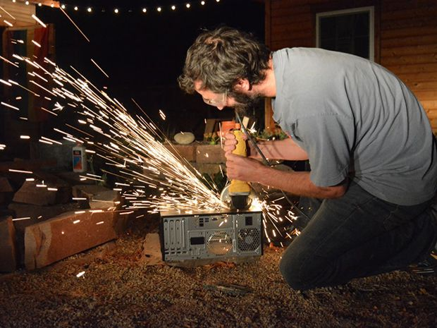 Za Wilcox on his knees destroying a computer with a power tool as sparks fly.