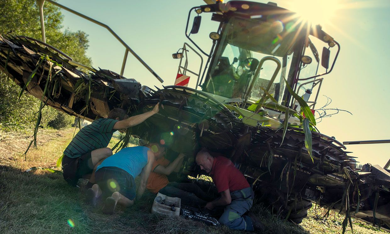 Four people working on a repair under a combine harvester.