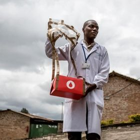 A man holding blood drone delivery at medical facility in Rwanda.