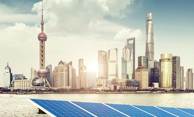 Image of Shanghai's skyline with solar panels in front.