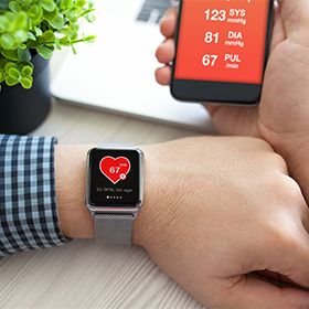 Man checking heart rate on smartwatch with app open on his phon