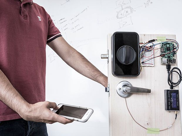 A researcher holds their thumb to the fingerprint sensor of a smartphone and touches a door handle at the same time.