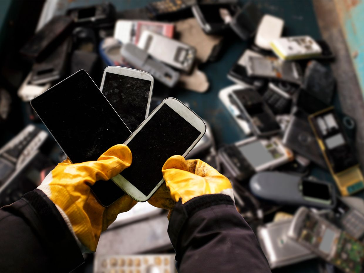 Gloved hands holding several used phones with a bin of other used electronics in the background