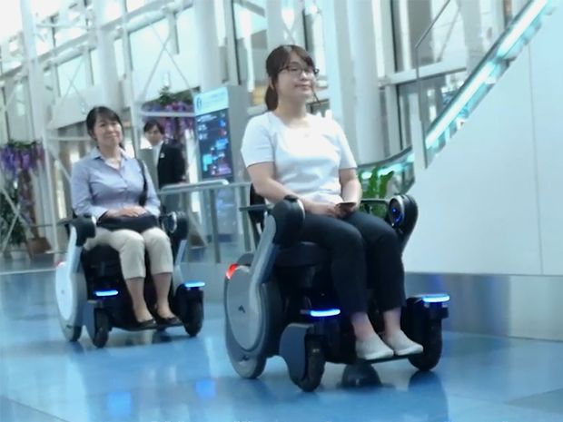 Users sit in two WHILL NEXT wheelchairs in the Haneda Airport in Japan