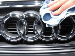 A hand polishing the Audi symbol, four interlocking rings.