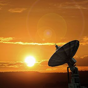 Photograph of an Amazon Web Services satellite during sunset.