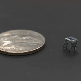 "A tiny silver robot stamped with the University of Maryland ""M"" on top stands next to a quarter dollar coin for scale."