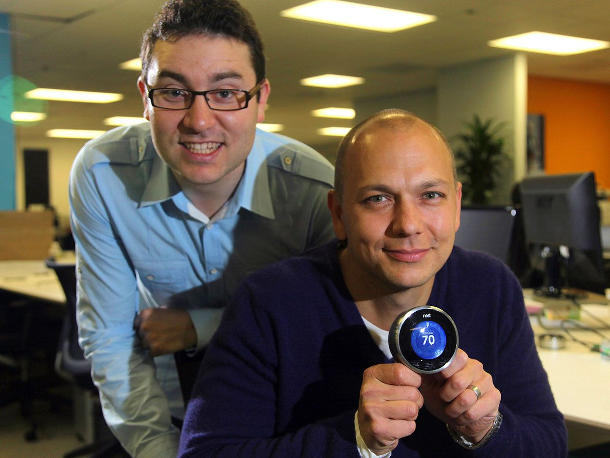 Tony Fadell [seated, holding the thermostat] and Matt Rogers [standing].