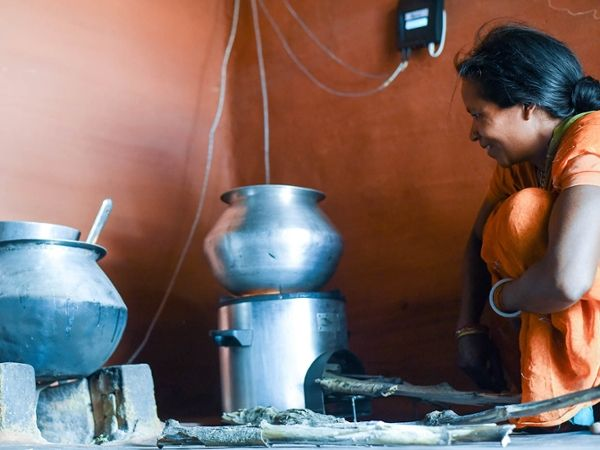 Photo showing woman with improved cookstove.