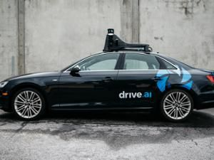side view of a black car in front of a concrete wall with the words drive ai written on the rear door