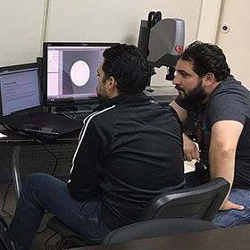 Marcos Santini [left], a student at the Puerto Rico Photonics Institute, works on optical dimensional metrology instruments with PRPI's lab technician, Francisco Rivera.