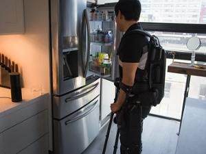 A man wearing a robotic exoskeleton controllable by voice command to a home automation product stands in front of the fridge; the Amazon Echo sits on the counter nearby.