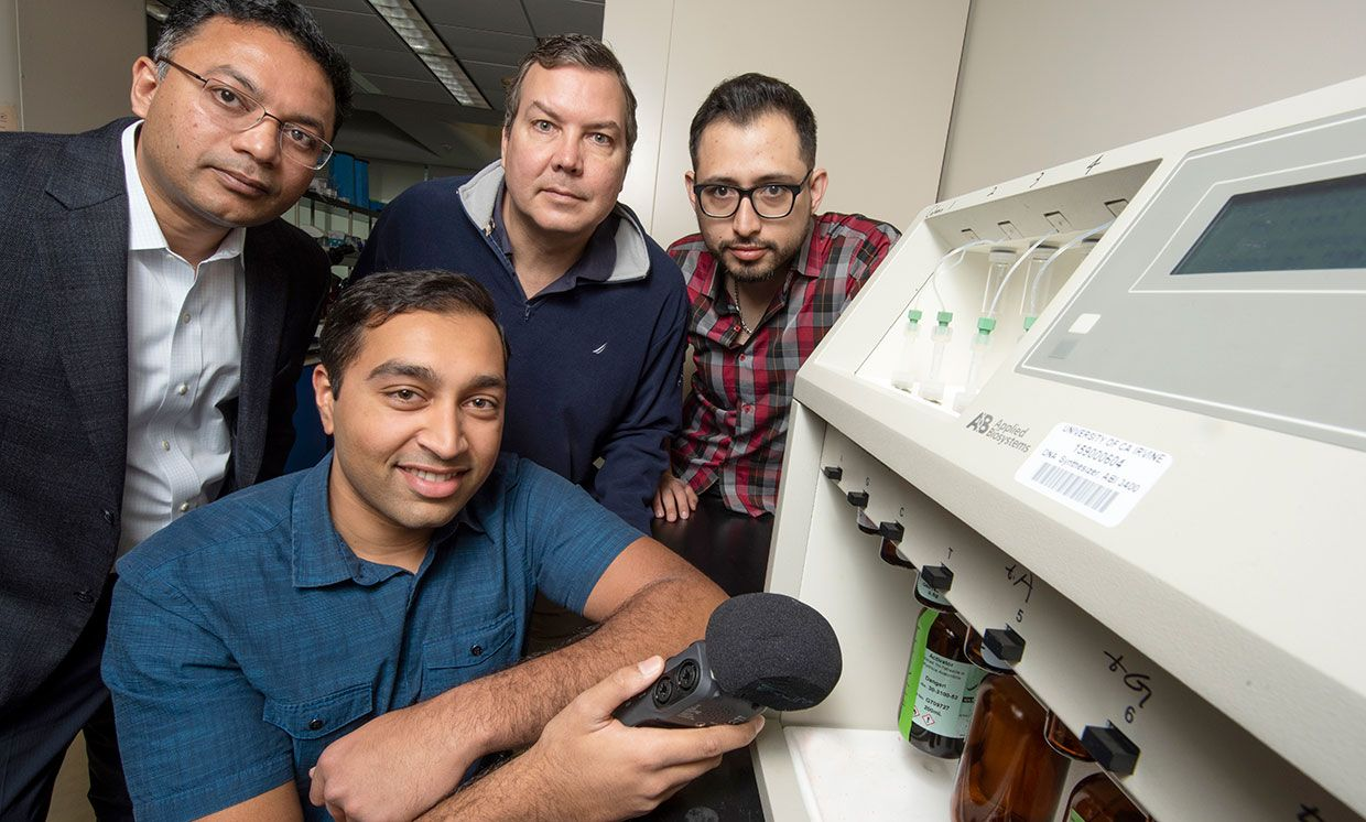 University of California Irvine researchers pose in front of a Applied Biosystems 3400 DNA Synthesizer. One researcher holds a microphone.