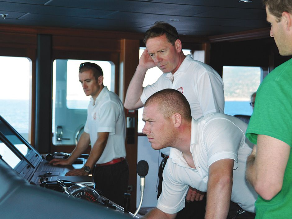 Schofield [center, standing] observes the effects of a live GPS spoofing demo on the bridge of the superyacht.