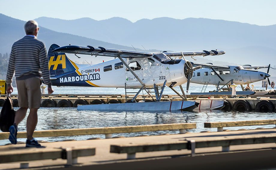 A man walks towards a Harbour Air Seaplane six-passenger Havilland Beaver aircraft, which will soon be retrofitted with a battery-powered electric motor.