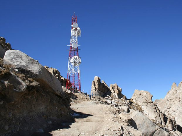 A red-and-white cell tower erected by Afghan Wireless is pictured.
