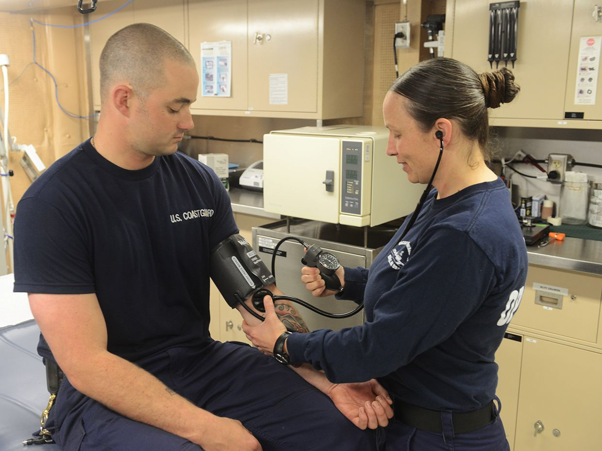 A health service technician aboard the Coast Guard Cutter Healy, measures Petty Officer 2nd Class Robert Martin's heart rate during a physical health assessment