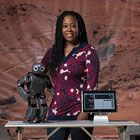 Image of Ayanna Howard smiling with a robot.