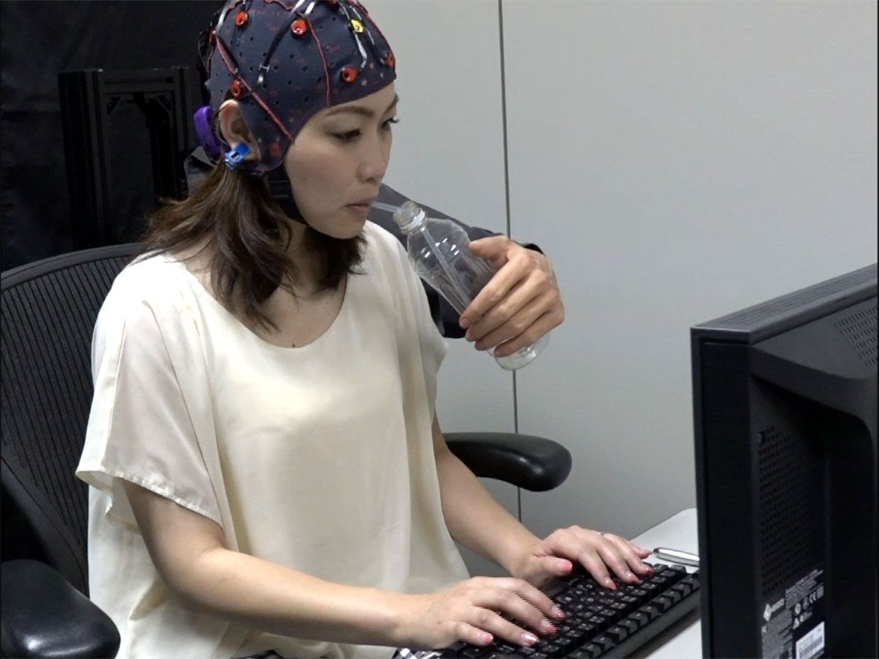 "Video still showing a woman wearing the BMI electrode cap while typing with two hands and controlling the robotic ""third"" arm to give her water."