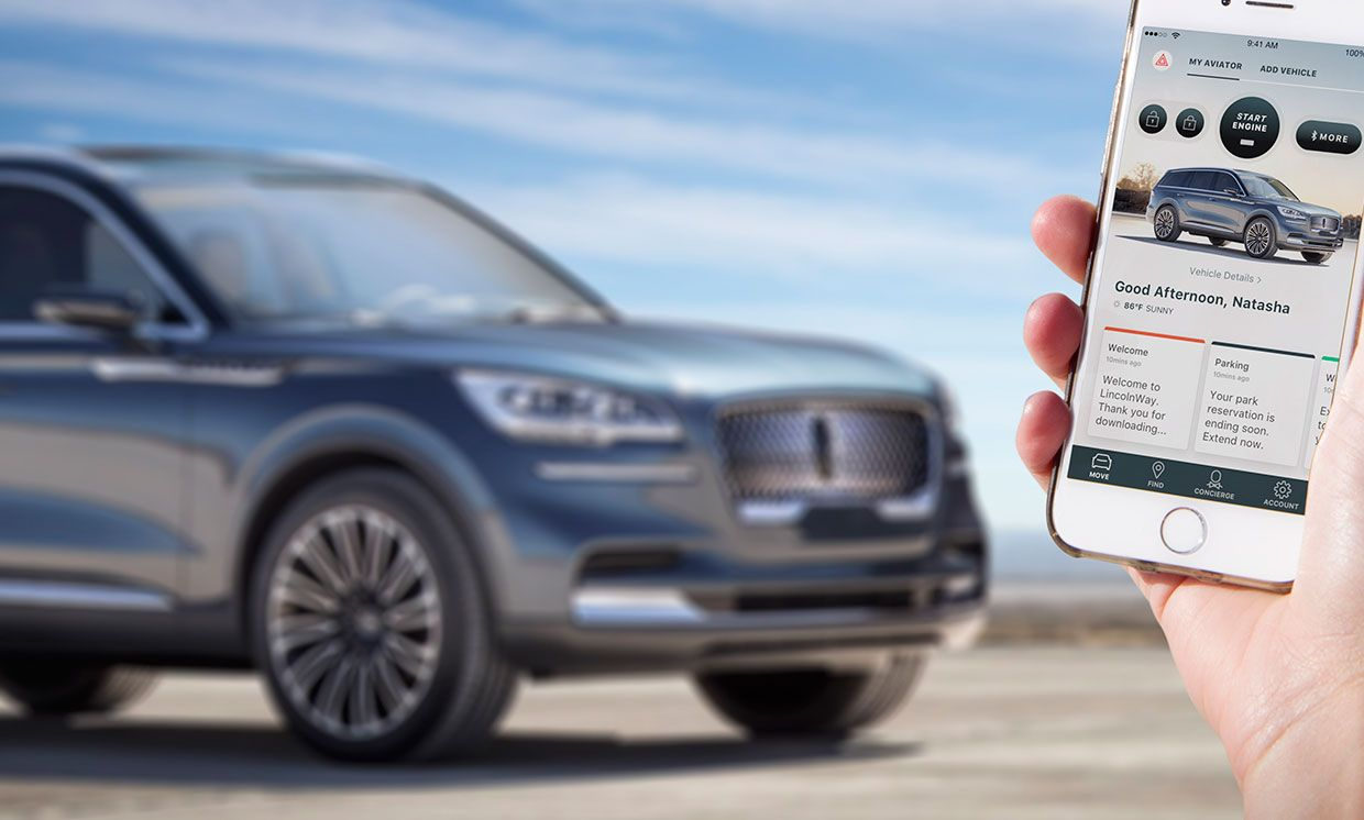 Photograph of a Lincoln Aviator in the background with a hand holding the Phone as Key app open on a smartphone.
