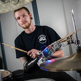 Jason Barnes with the robotic drumming prosthesis.