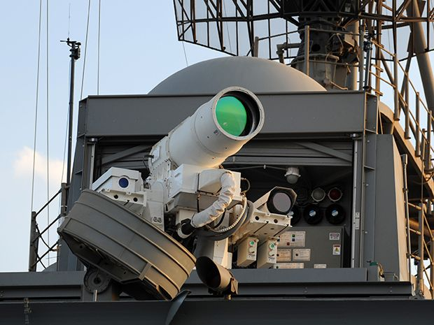 A photo of the laser weapon mounted on the USS Ponce, which looks like a white telescope pointing out from high on the ship.