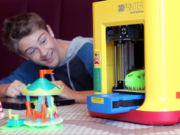 A child checks out the $250 da Vinci MiniMaker, a 3D printer for kids from XYZprinting, along with a printed merry-go-round