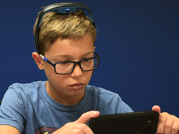 A boy wearing a headband with an EEG sensor holds a smartphone and plays a game.