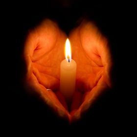 A pair of hands forming a heart shape while holding a lit candle.